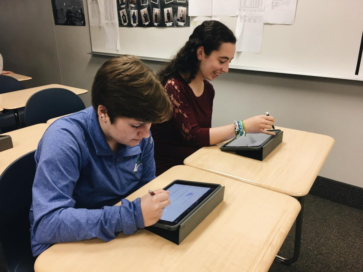 Seniors Jessica Lundquist and Miriam Lebowitz make use of their new iPads in their honors physics class.