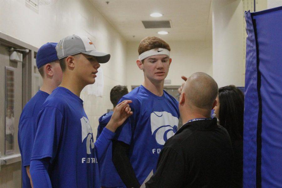 Mr.Comer talks with several dodgeball teammates.