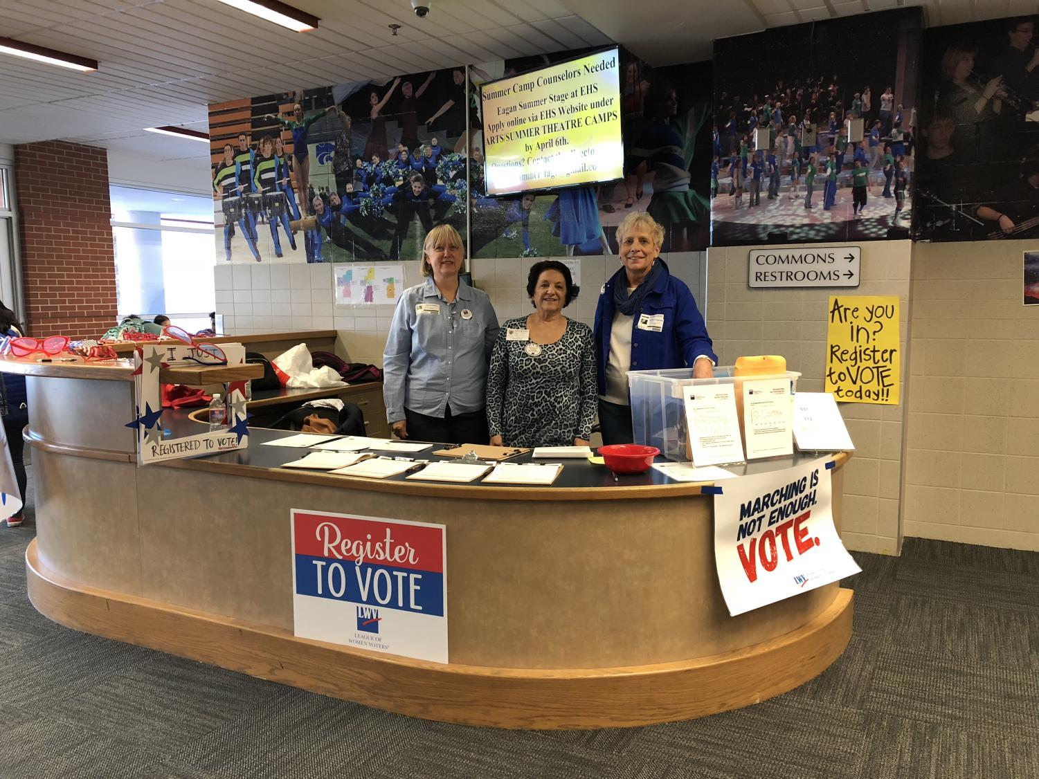 Volunteers from the League of Women Voters  help students register to vote.